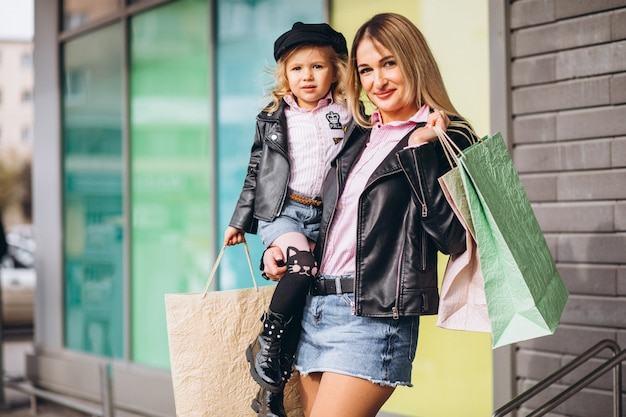 Madre con su pequeña hija linda con bolsas de compras