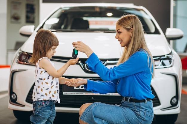 Madre con su pequeña hija de pie delante de un automóvil