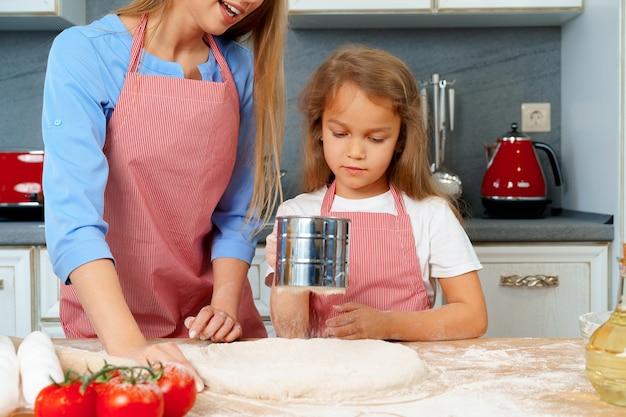 Madre y su pequeña hija preparando masa en la cocina