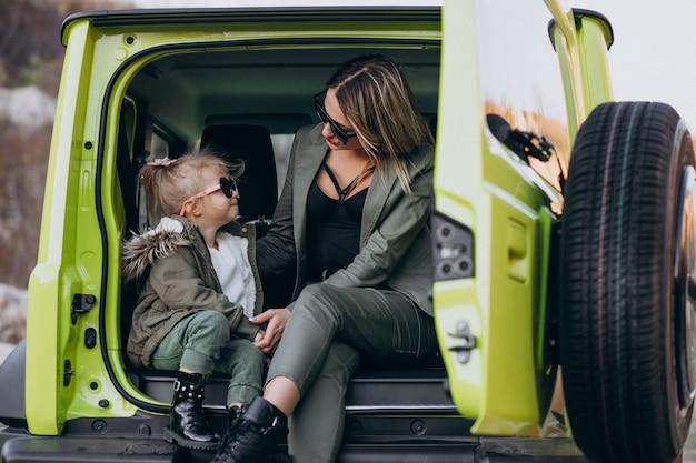 Madre con su pequeña hija sentada en la parte trasera del auto