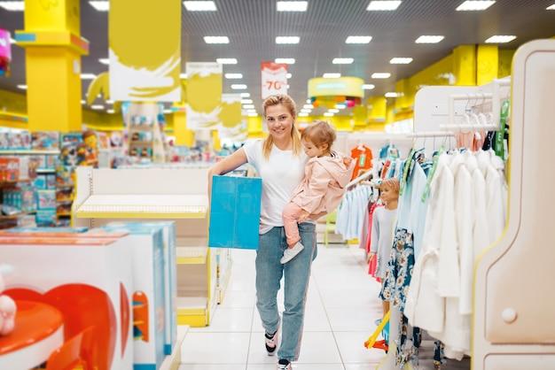 Madre con su pequeña hija tienen una compra en la tienda para niños. mamá e hijo comprando juguetes en el supermercado juntos, compras familiares
