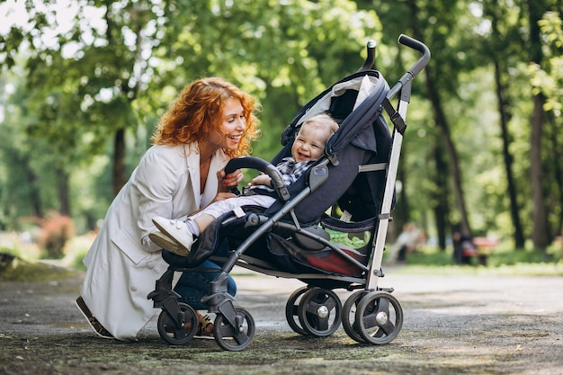 Madre con su pequeño hijo en un cochecito de bebé en el parque