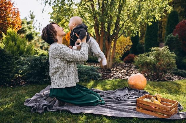 Madre con su pequeño hijo haciendo picnic en un patio trasero