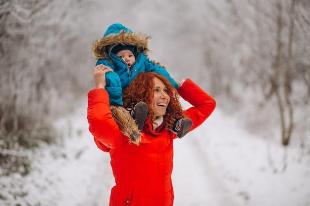 Madre con su pequeño hijo juntos en un parque de invierno