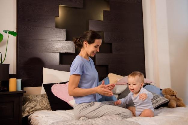 Madre con su pequeño hijo lindo jugando en la cama.