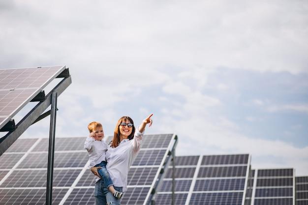 Madre con su pequeño hijo por paneles solares