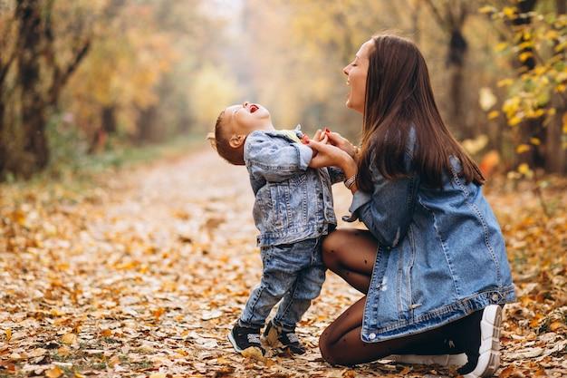 Madre con su pequeño hijo en el parque otoño