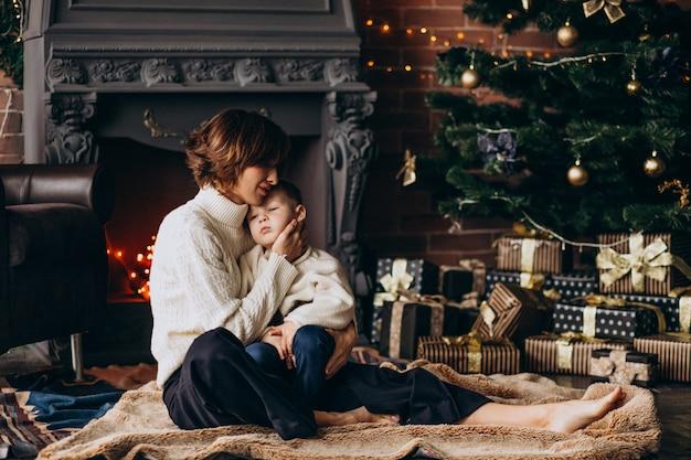 Madre con su pequeño hijo sentado junto al árbol de navidad