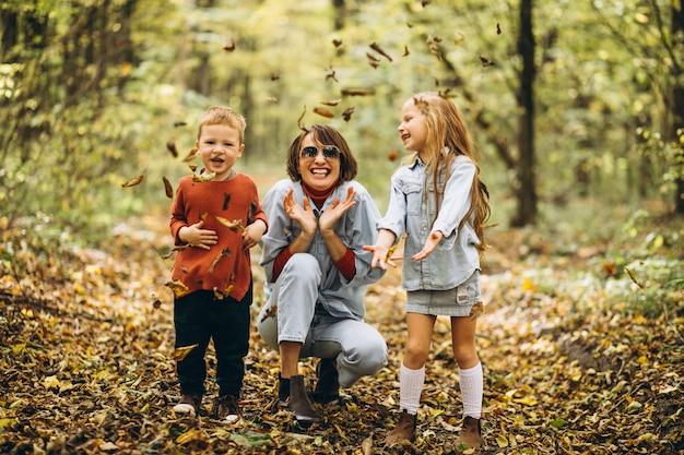 Madre con su pequeño hijo y su hija en un parque de otoño