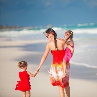Madre y sus dos hijas lindas caminando en la playa exótica en un día soleado