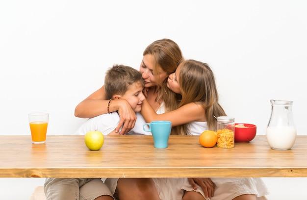 Madre con sus dos hijos desayunando y abrazándose.