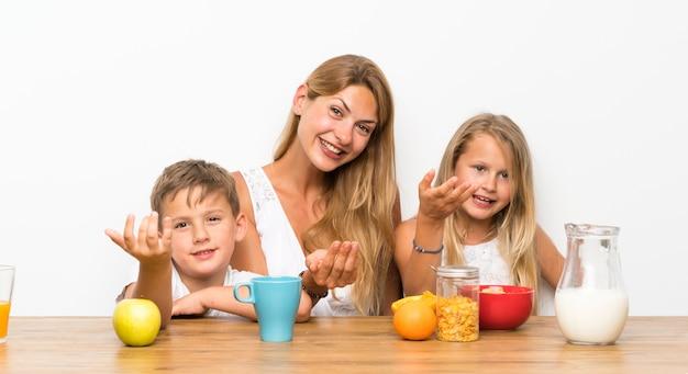 Madre con sus dos hijos desayunando haciendo gesto venidero