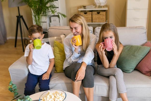 Madre y sus hijos bebiendo de tazas vista frontal