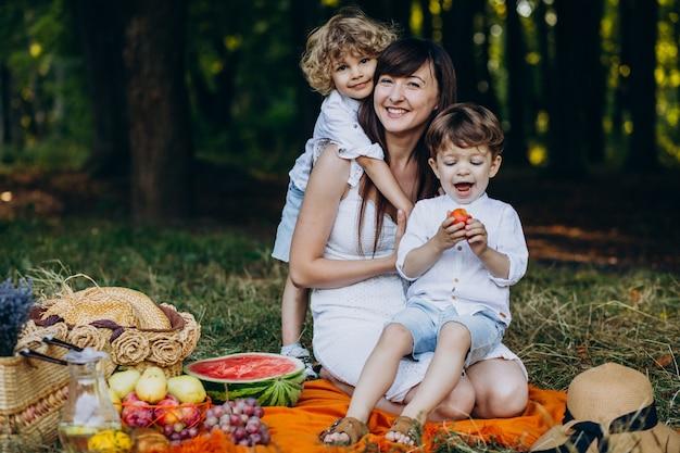 Madre con sus hijos haciendo un picnic en el bosque