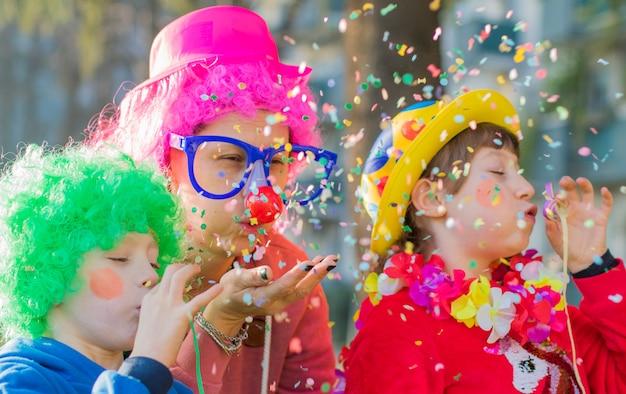Una madre y sus hijos juegan con confeti en traje de carnaval