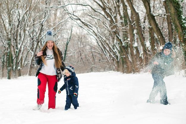 Madre y sus hijos juegan con la nieve en un parque. horario de invierno. vacaciones familiares de invierno.