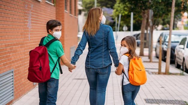 Madre con sus hijos van a la escuela con máscaras