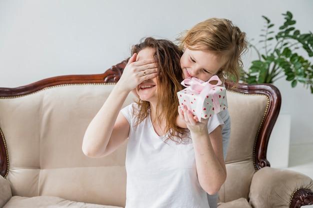 Madre tapándose los ojos mientras recibe el regalo del día de la madre en casa.