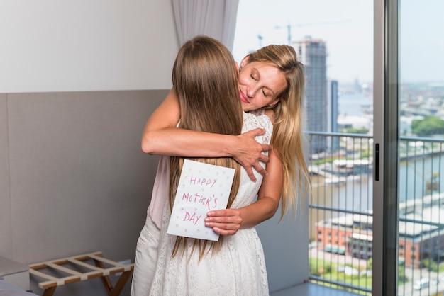 Madre con tarjeta de felicitación abrazando a hija