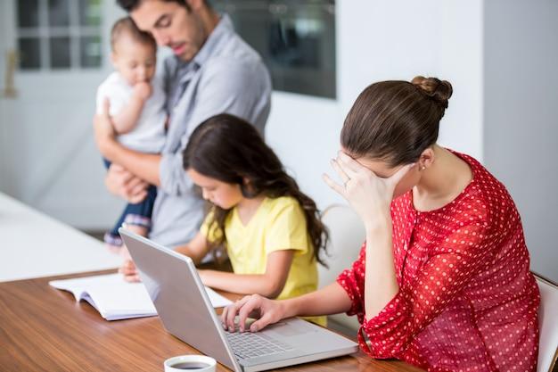 Madre tensa trabajando en la computadora portátil con el padre ayudando a la hija en la tarea