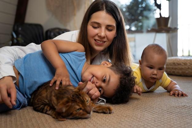 Madre de tiro medio con niños y gato