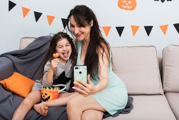 Madre tomando una selfie con hija en halloween