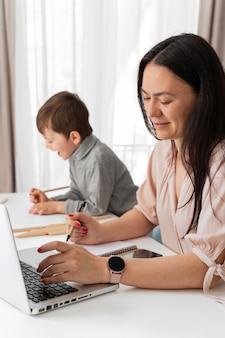 Madre trabajando en casa con niño