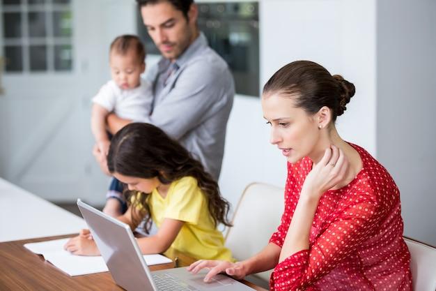 Madre trabajando en la computadora portátil con hija estudiando