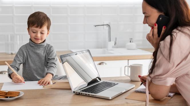 Madre trabajando con ordenador portátil de cerca