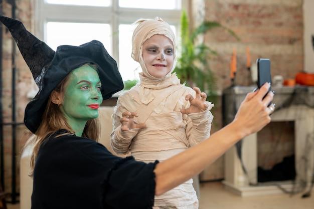 Madre en traje de bruja haciendo selfie con su hijo en traje de zombie