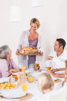 Madre trayendo pavo a la mesa