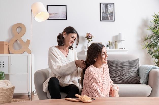 Madre trenzando el cabello de su hija