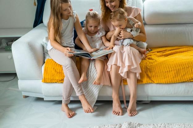 Madre con tres hijos leyendo un libro en un ambiente hogareño.