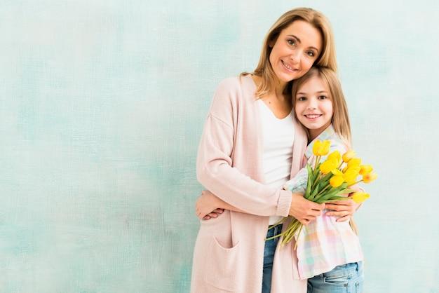 Madre con tulipanes y abrazos de hija