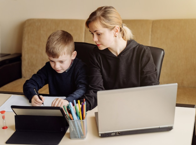 Madre usando una computadora portátil y una tableta enseñando con su hijo en línea en su casa en su habitación