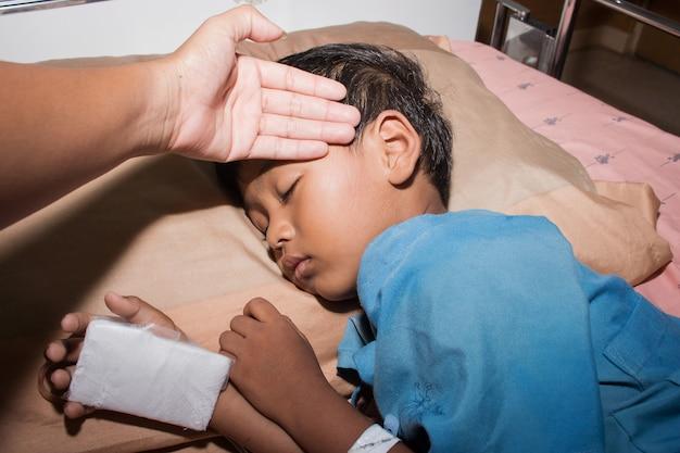 La madre verificó la fiebre de su hijo enfermo mientras descansaba en la cama