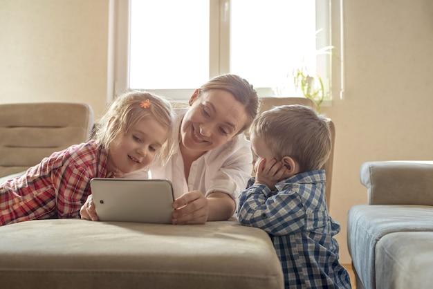 Madre viendo dibujos animados en una tableta con sus dos hijos pequeños