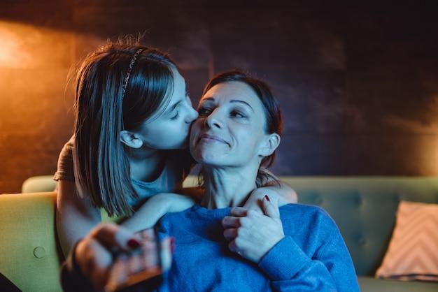 Madre viendo televisión mientras su hija le da un beso de buenas noches