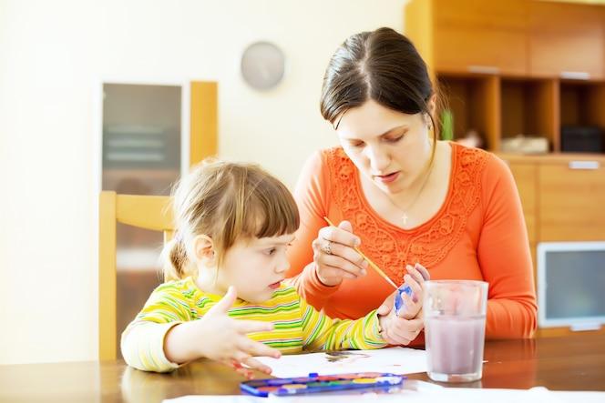 Madre y bebé dibujando con las manos y acuarela