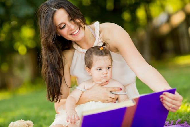 Madre y bebé niña con libro en el parque