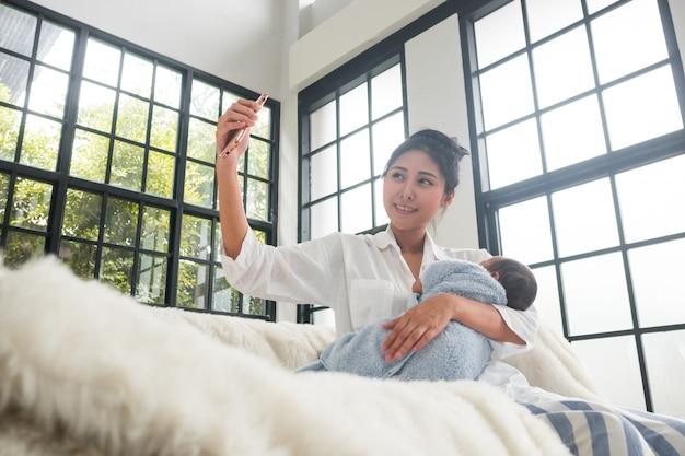 Las madres adolescentes y los bebés están tomando selfies.
