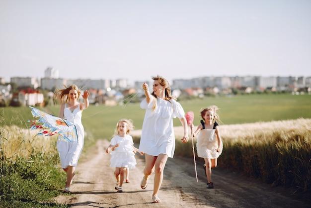 Madres con hijas jugando en un campo de otoño