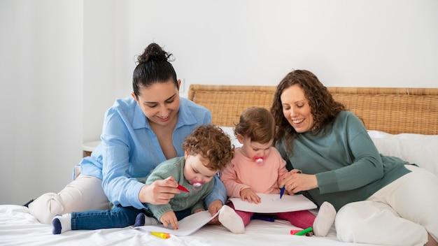 Madres lgbt en casa en el dormitorio con sus hijos
