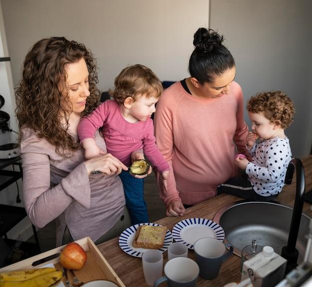 Madres lgbt en casa pasando tiempo en la cocina con sus hijos