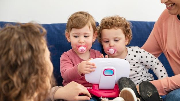 Madres lgbt en casa en el sofá jugando con los niños