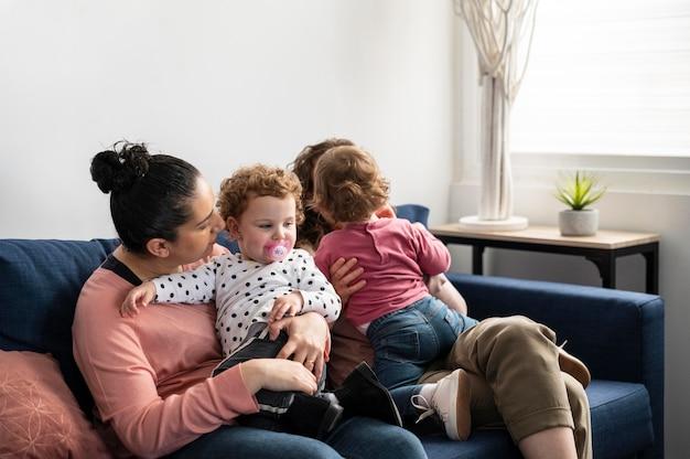 Madres lgbt en casa en el sofá con niños