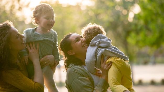 Madres lgbt sonrientes al aire libre en el parque con sus hijos