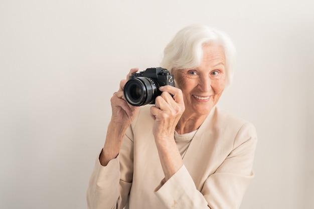 Madura fotógrafa sonriente de pelo blanco con photocamera por cara de pie en la pared de luz
