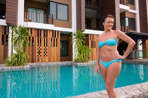 Madura hermosa mujer turista escandinavo en bikini de pie junto a la piscina