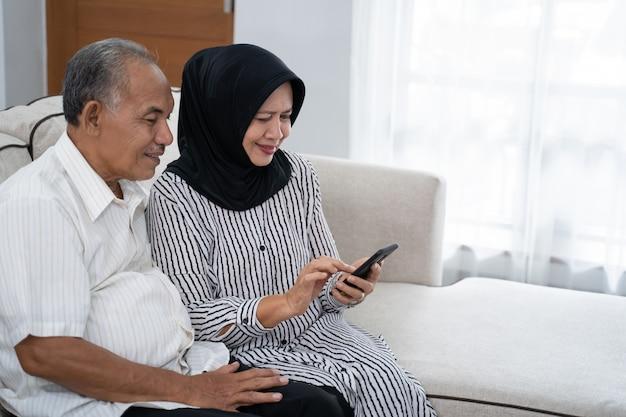 Madura pareja asiática con smartphone